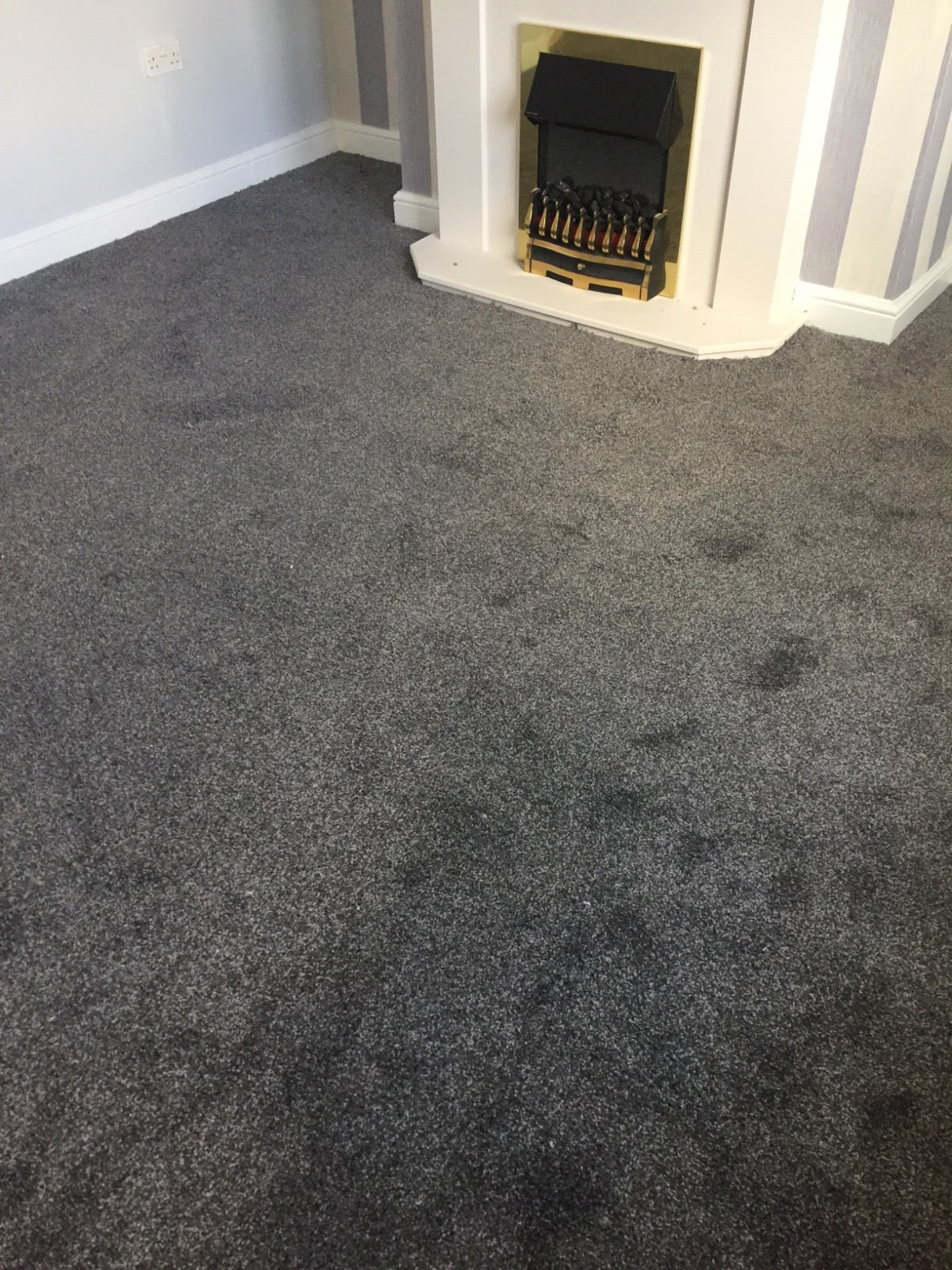 grey carpet in living room around fireplace