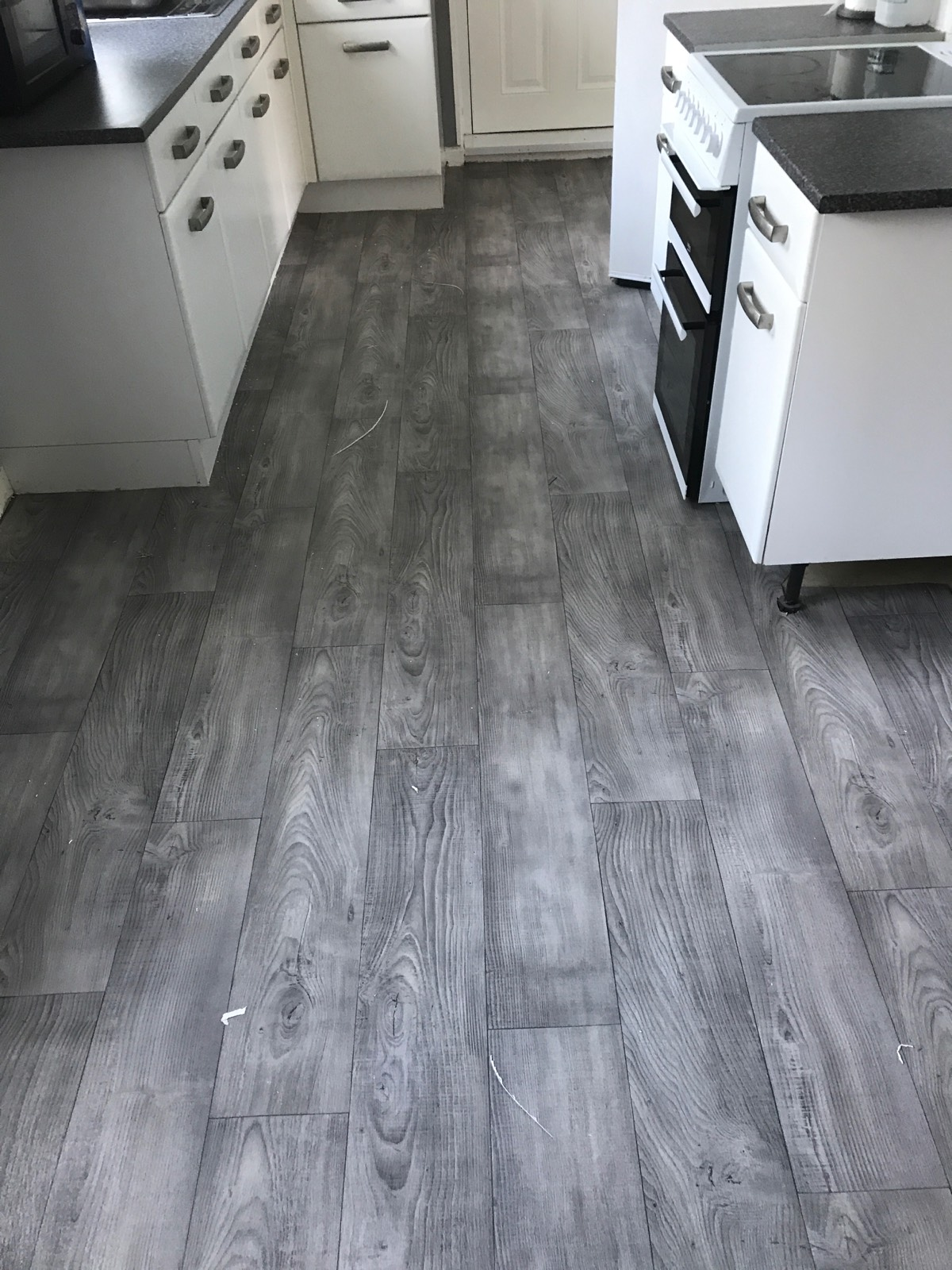 light grey vinyl flooring with laminate design in kitchen with white units