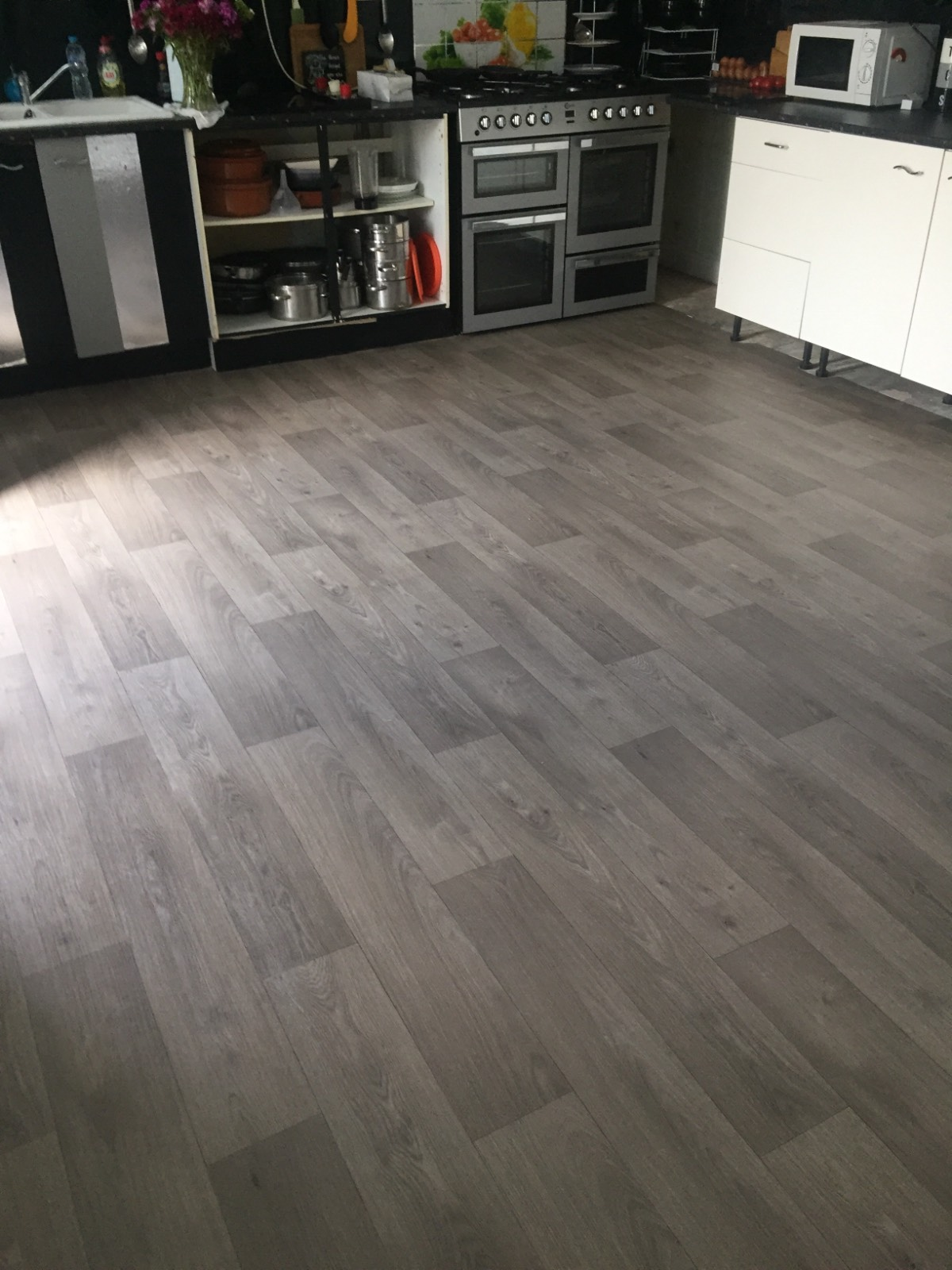 grey and brown vinyl flooring with wooden design in kitchen