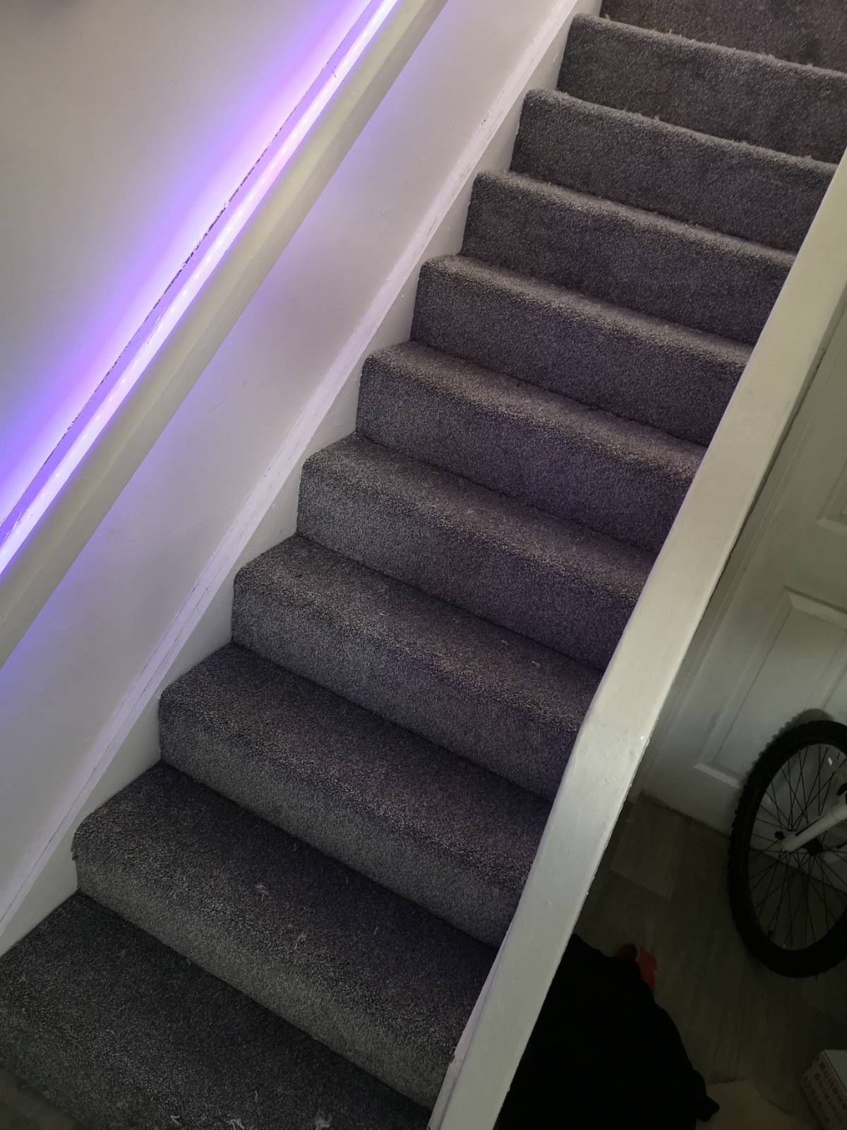 grey carpet fitting on staircase with purple lighting under banister