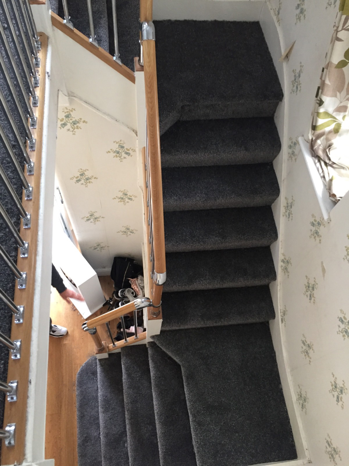 dark grey carpet fitted on staircase with brown banister