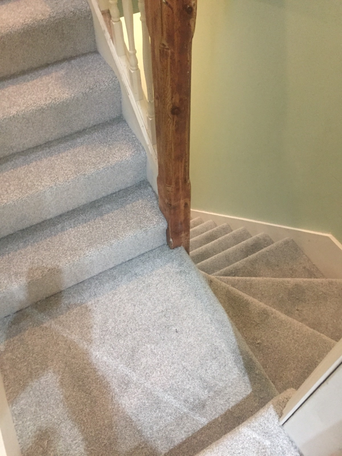 silver carpet fitted on staircase with brown banister