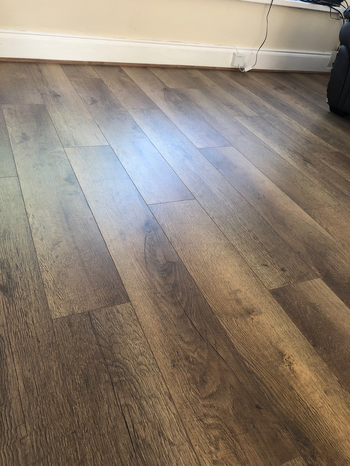 close up of dark brown and grey mixed laminate flooring fitted in living room