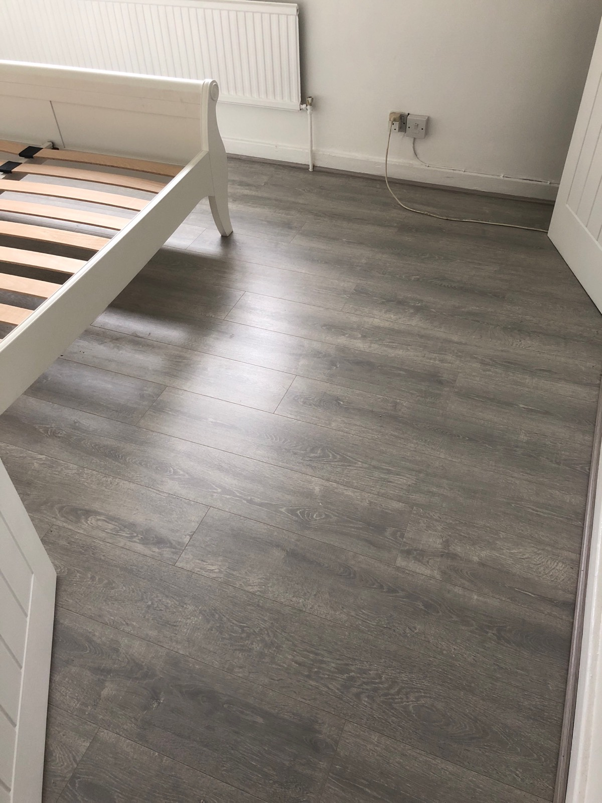 dark grey laminate flooring fitted in bedroom
