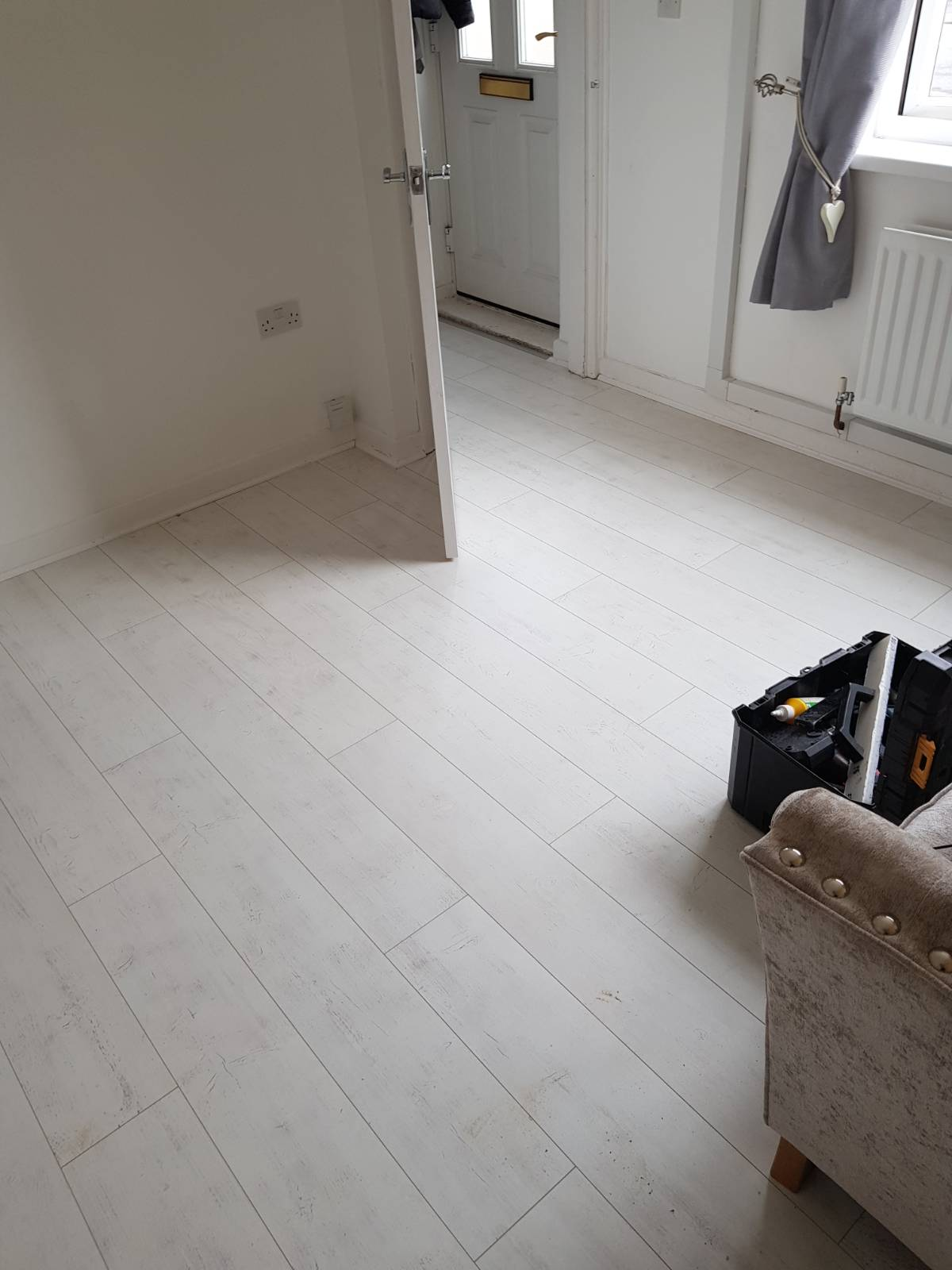 white laminate flooring fitting in living room area