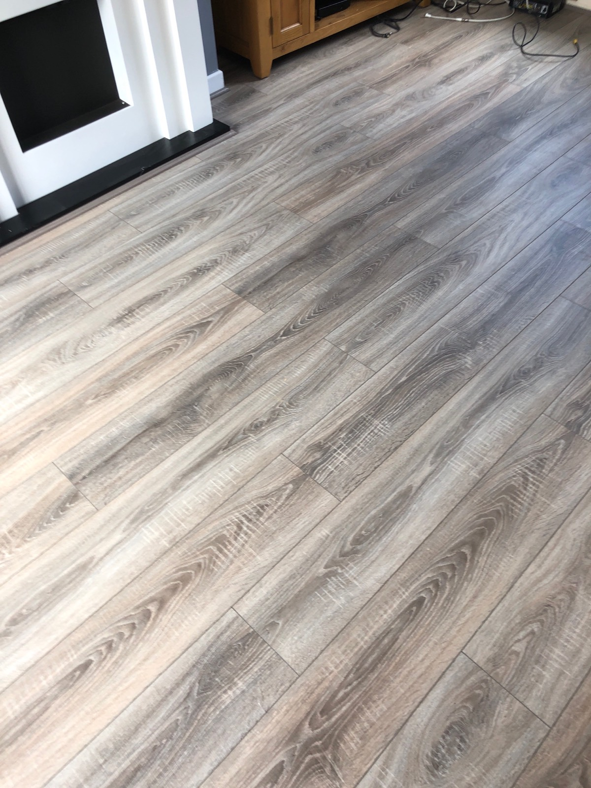 light laminate flooring fitted in living room with fireplace in image