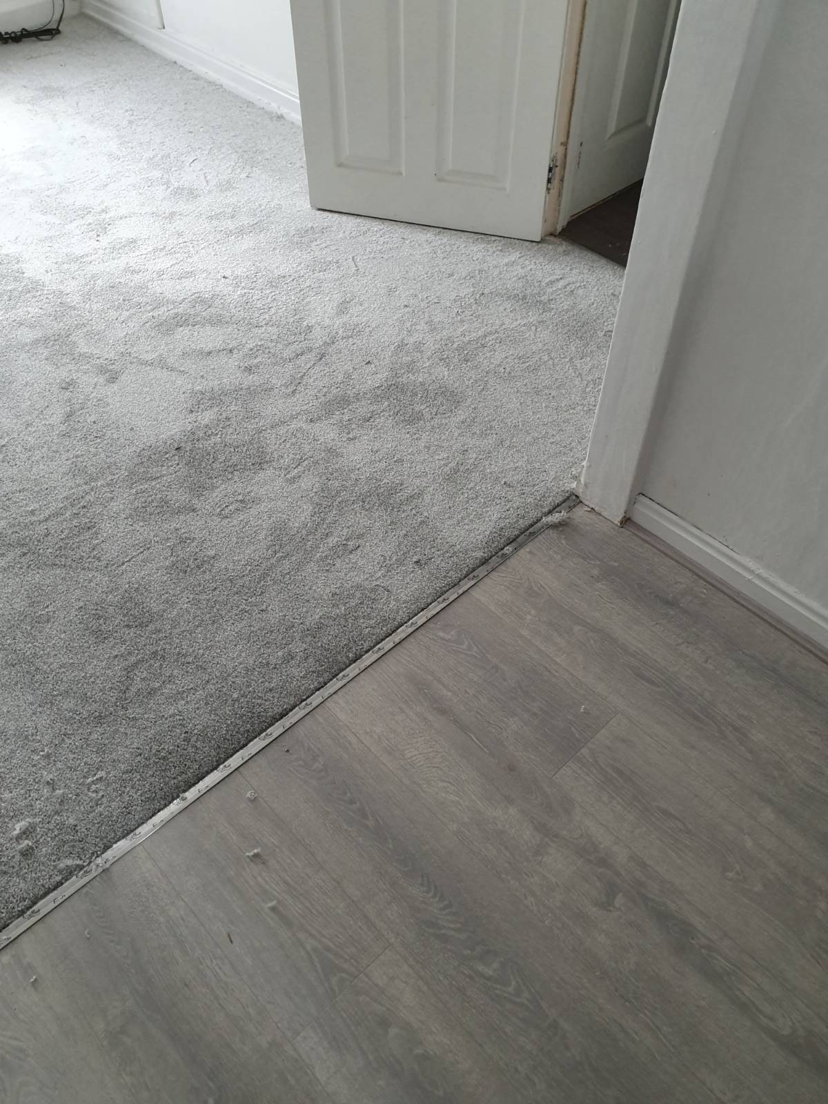 living area split by half grey laminate flooring and half carpet