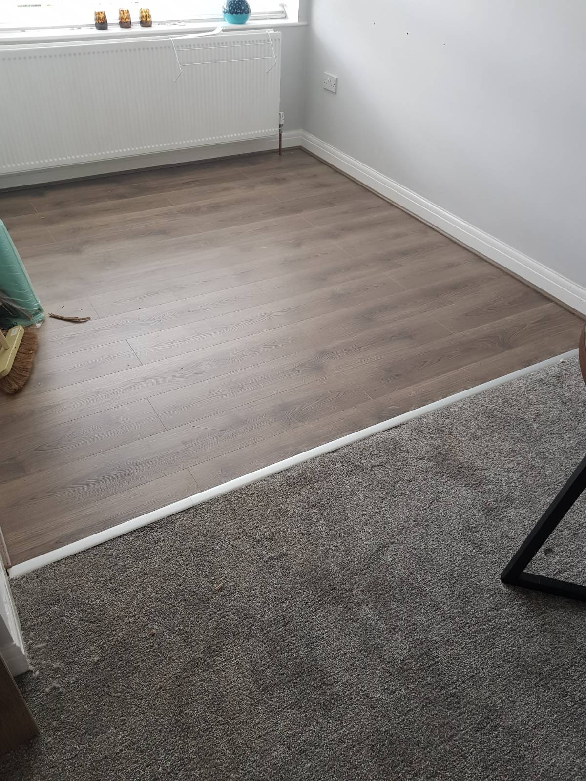 living room flooring split by half grey carpet and half brown laminate