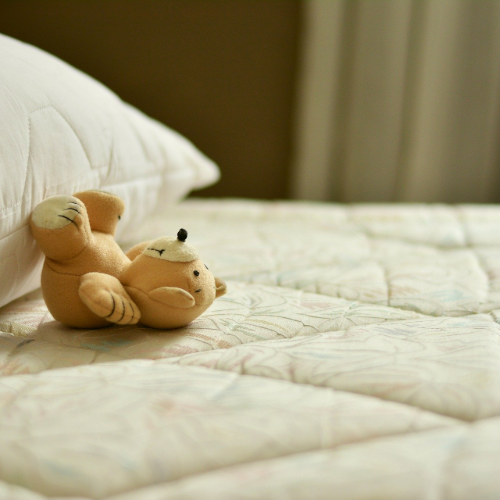Teddy bear lying on bare mattress